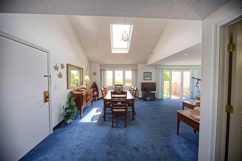 Living and dining room with blue carpet in our wells ME vacation rentals