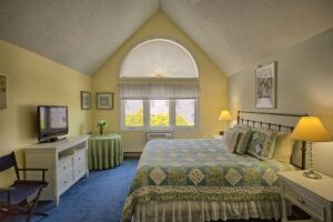 Bedroom with yellow walls and large windows in Wells Maine near the beach