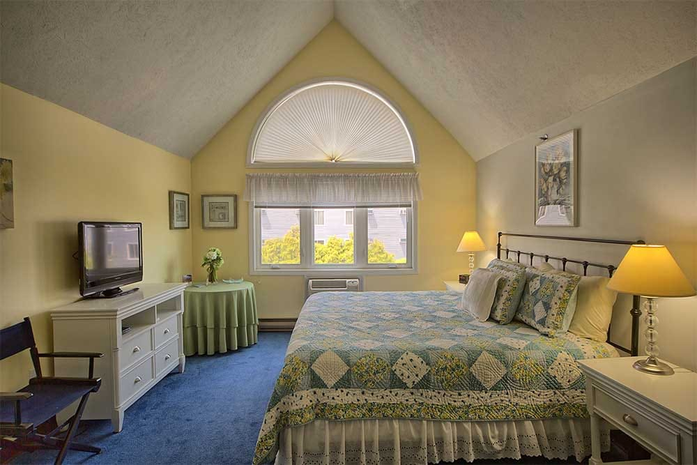 Bedroom with yellow walls and large windows