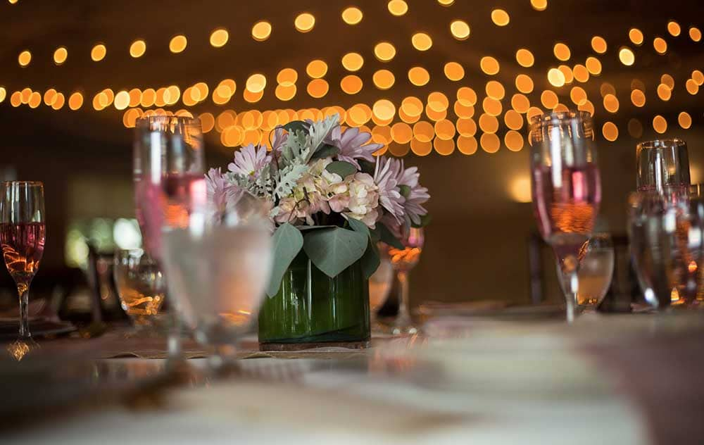 Flowers and Champagne on table under decorative lights