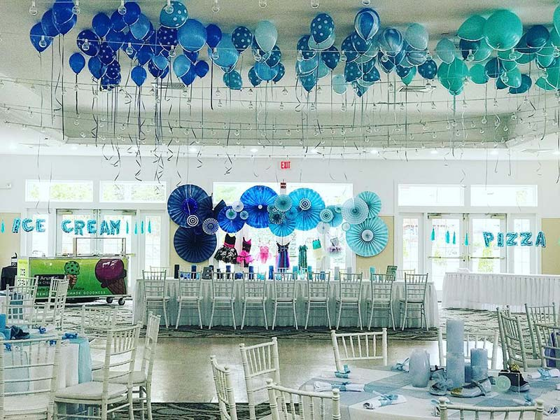 Blue theme event space with balloons,, tables and chairs
