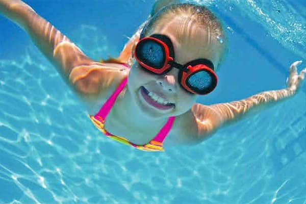Child swimming under water with goggles on